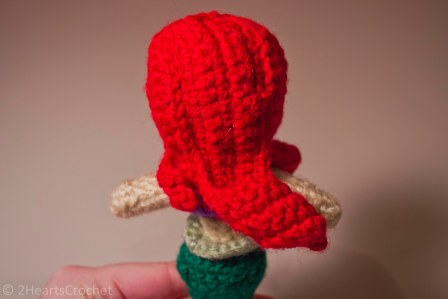 All of the hair pieces sewn onto the doll, without the button, from the back.