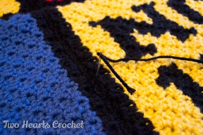 Carefully feed the yarn through the blanket with your needle.